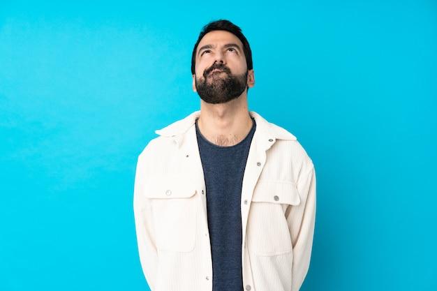 孤立した青い壁と見上げる白いコーデュロイジャケットと若いハンサムな男