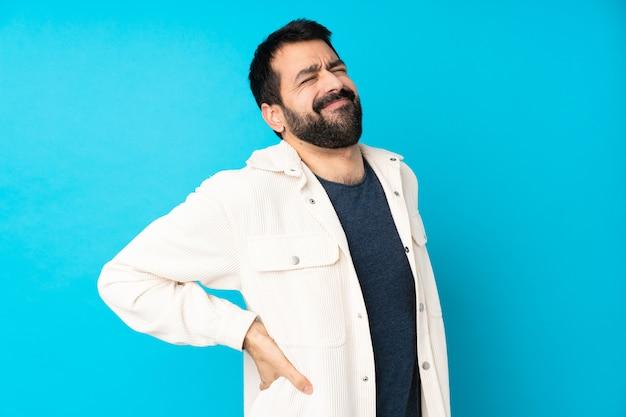 Молодой красивый человек с белой вельветовой курткой над изолированной синей стеной страдает от боли в спине за то, что приложил усилие
