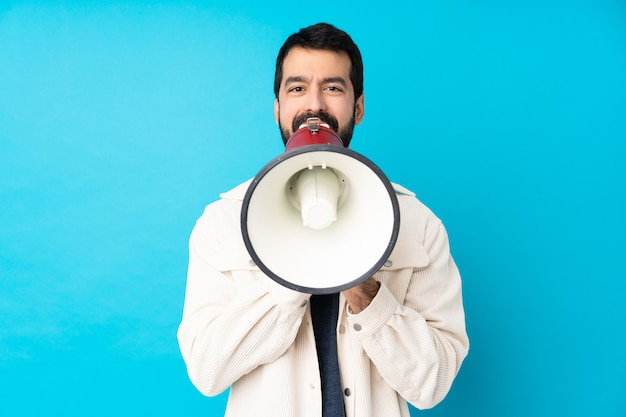 メガホンを通して叫んで孤立した青い壁に白いコーデュロイジャケットと若いハンサムな男