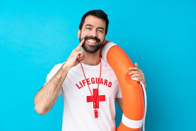 Спасатель человек над синей стеной, улыбаясь со счастливым и приятным выражением