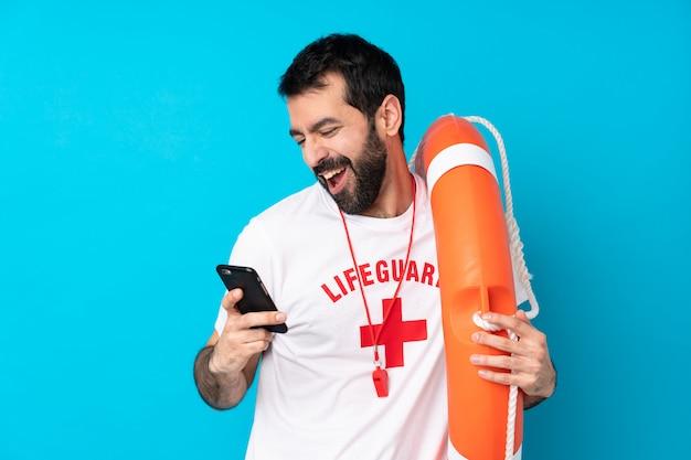 Спасатель человек над синей стеной с телефоном в победной позиции