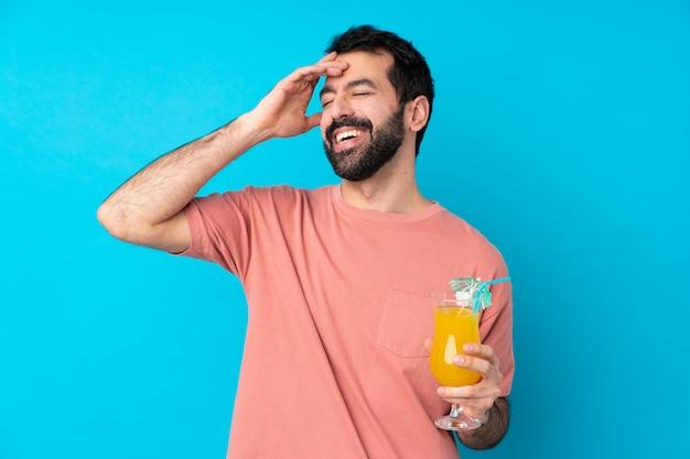 Молодой человек за коктейль над синей стеной, улыбаясь много