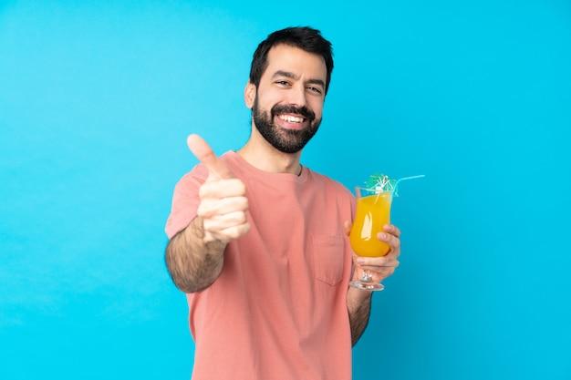 Молодой человек за коктейль над синей стеной с пальцами вверх, потому что случилось что-то хорошее