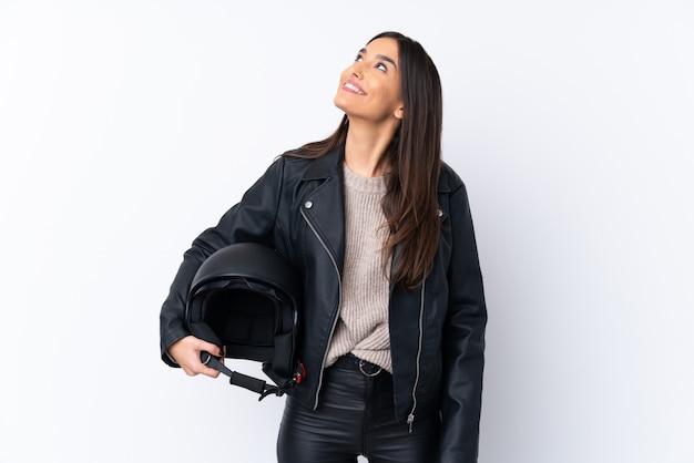 笑顔ながら見上げる孤立した白い壁にオートバイのヘルメットを持つ若いブルネットの女性