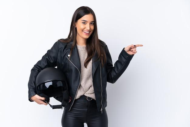 Молодая брюнетка женщина с мотоциклетным шлемом над изолированной белой стеной удивлен и указывая пальцем в сторону
