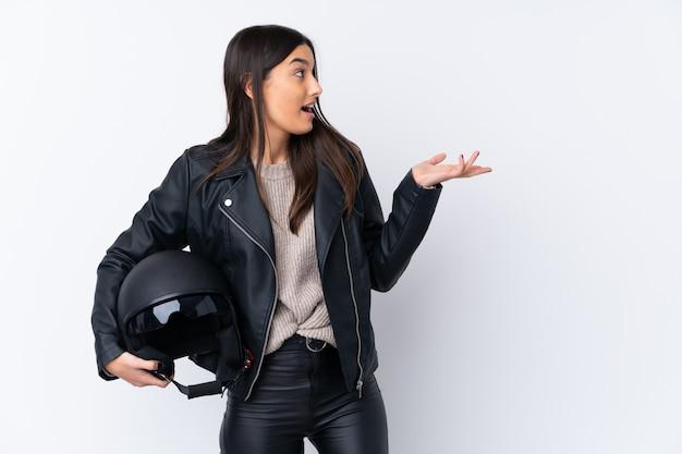 Молодая брюнетка с мотоциклетным шлемом на белом фоне с удивленным выражением лица