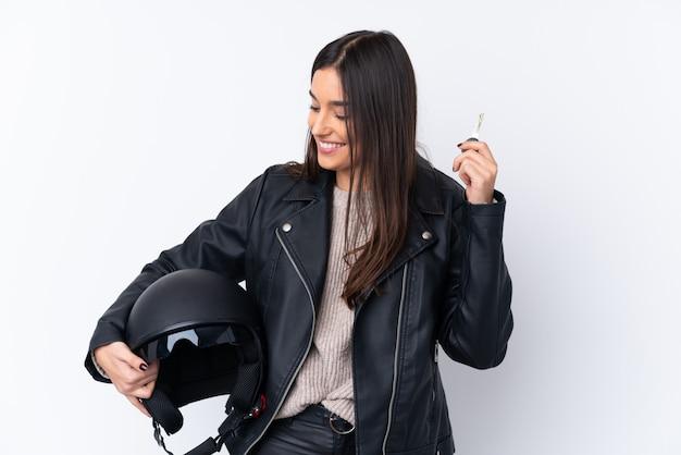 オートバイのヘルメットと分離の白い壁の上のキーを保持している若いブルネットの女性