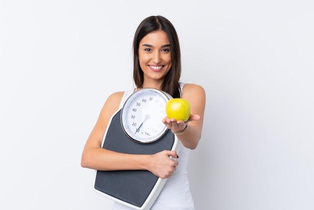 計量機を押しながらリンゴを提供している孤立した白い壁の上の若いブルネットの女性