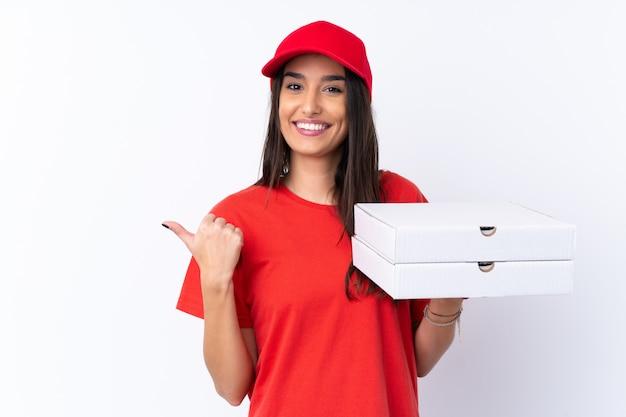 Женщина доставки пиццы держит пиццу на изолированной белой стене, указывая на сторону, чтобы представить продукт