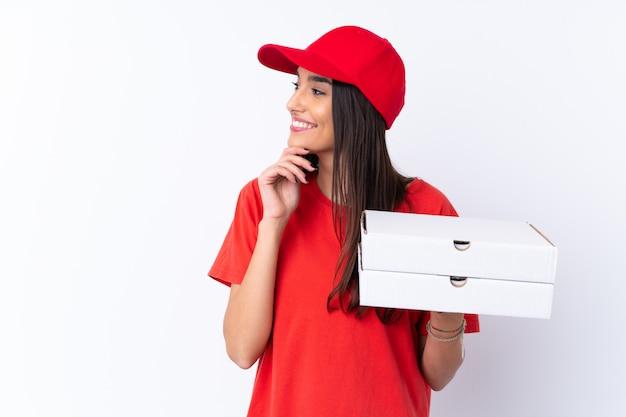 アイデアを考えて、側を見て孤立した白い壁にピザを保持しているピザ配達の女性