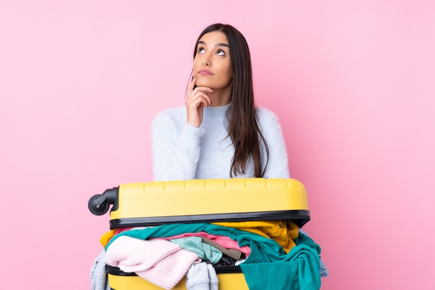 アイデアを考えて分離のピンクの壁の上の服でいっぱいのスーツケースを持つ旅行者女性