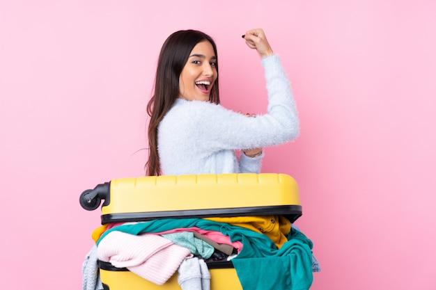 強いジェスチャーを作る分離のピンクの壁の上の服でいっぱいのスーツケースを持つ旅行者女性