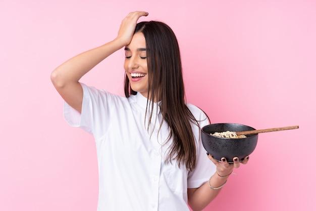 Молодая брюнетка над изолированной розовой стеной что-то поняла и решила найти решение, держа миску лапши с палочками для еды