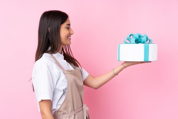 Молодая женщина с большой торт над изолированной стеной с счастливым выражением
