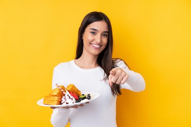 Молодая брюнетка женщина, держащая вафли над изолированной стеной, указывает пальцем на вас с уверенным выражением лица
