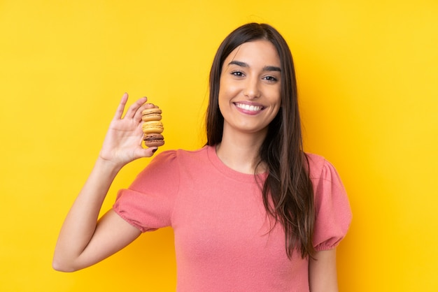 Молодая брюнетка над желтой стеной, держащей разноцветные французские макаруны и много улыбающейся