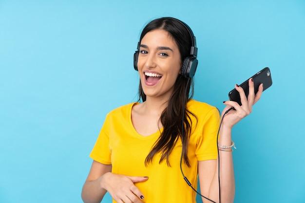 Молодая брюнетка над изолированной синей стеной, слушая музыку и делая жест гитары