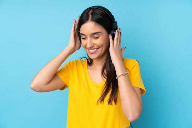 Молодая женщина брюнет над изолированной музыкой голубой стены слушая