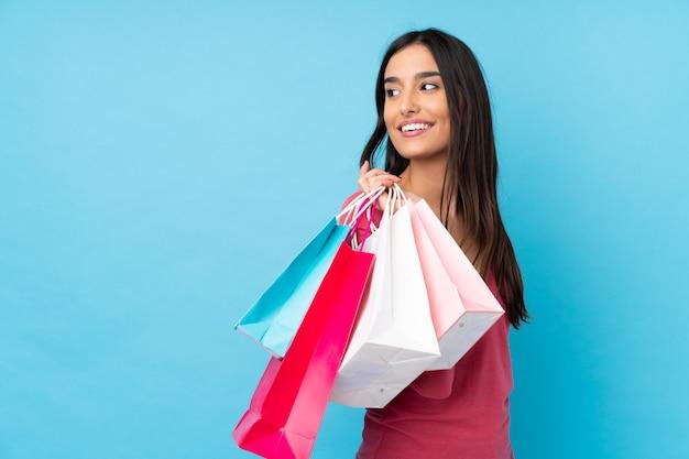 買い物袋を押しながら振り返ってみると分離の青い壁の上の若いブルネットの女性