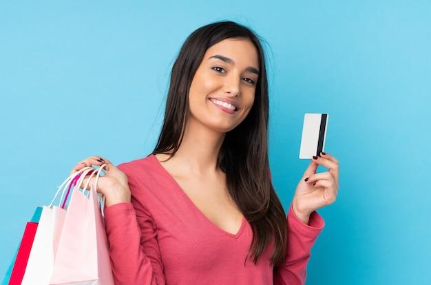 Молодая женщина брюнет над изолированной голубой стеной держа хозяйственные сумки и кредитную карточку