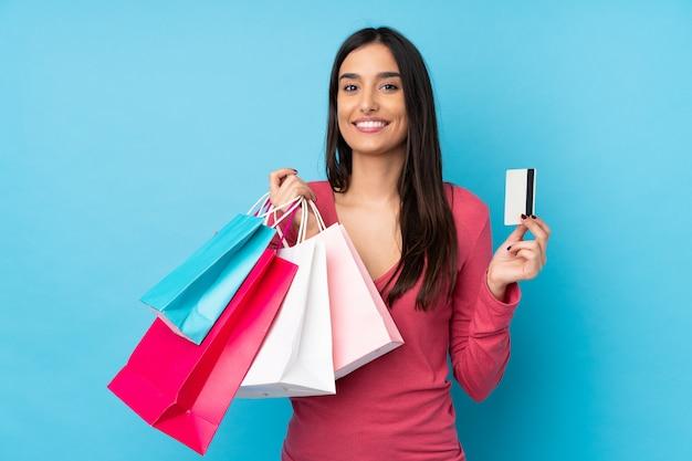 買い物袋とクレジットカードを保持している孤立した青い壁の上の若いブルネットの女性
