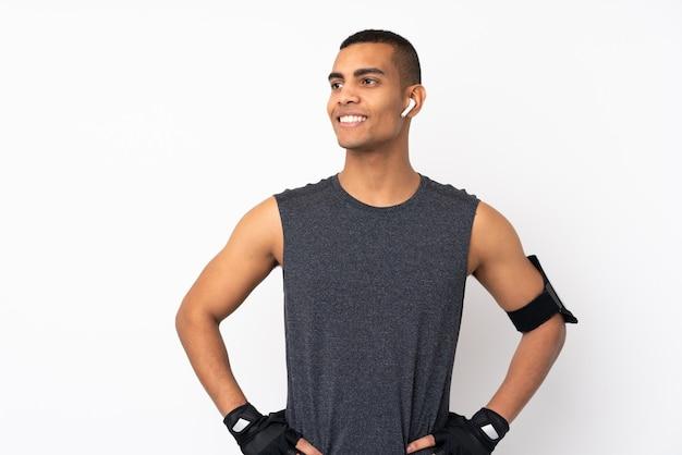 若いアフリカ系アメリカ人のスポーツ男の腰に腕でポーズと側を見て分離の白い壁に