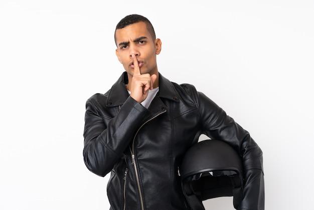沈黙のジェスチャーをしている孤立した白い壁の上のオートバイのヘルメットを持つ若いハンサムな男