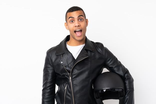 驚きの表情で孤立した白い壁にオートバイのヘルメットを持つ若いハンサムな男