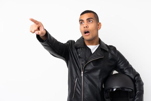 Молодой красавец с мотоциклетным шлемом на белом фоне, указывая прочь