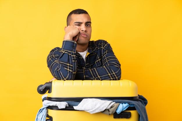 孤立した黄色の壁の上の服でいっぱいのスーツケースを持つ旅行者男