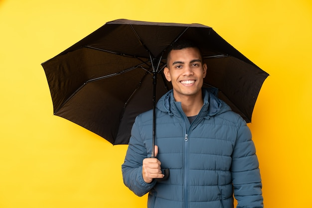 多くの笑みを浮かべて孤立した黄色の壁に傘を置く若いハンサムな男