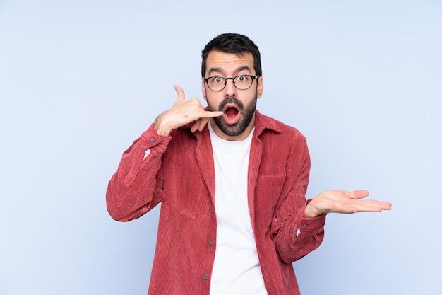 電話のジェスチャーを作ると疑う青い壁にコーデュロイのジャケットを着ている若い白人男