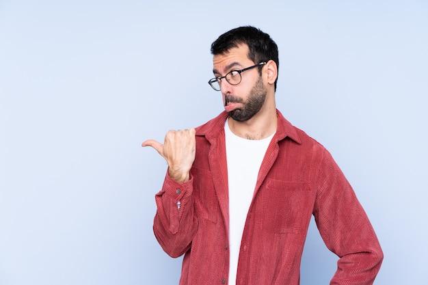 不幸と側を指している青い壁にコーデュロイのジャケットを着ている若い白人男