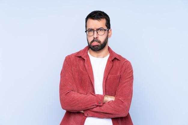 青い壁の気分を害するコーデュロイジャケットを着ている若い白人男