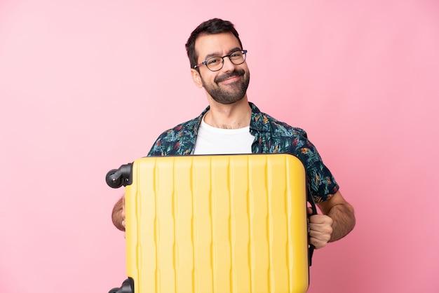 旅行スーツケースと休暇で孤立した壁の上の若い白人男