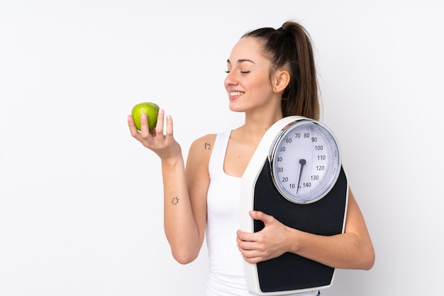 計量機とリンゴの分離の白い壁の上の若いブルネットの女性