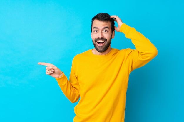 Молодой человек кавказской над синей стеной удивлен и указывая пальцем в сторону