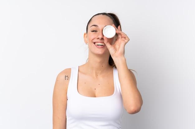 保湿剤と幸福と分離の白い壁の上の若いブルネットの女性