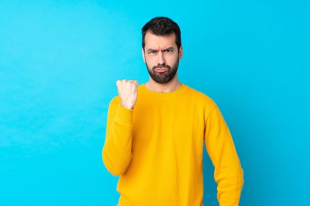 怒っているジェスチャーで孤立した青い壁の上の若い白人男