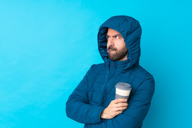冬のジャケットを着て、混乱した表情で孤立した青い壁に持ち帰り用のコーヒーを保持している男
