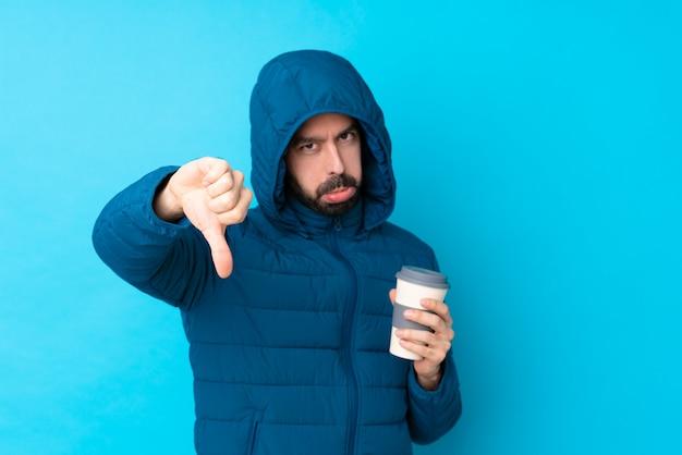 冬のジャケットを着て、否定的な表現で親指を示す分離の青い壁にテイクアウトコーヒーを保持している男