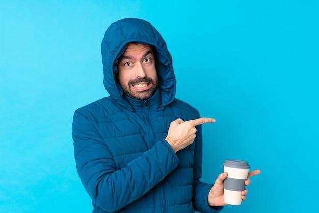 冬のジャケットを着て、怖がって、側を指している孤立した青い壁に持ち帰り用のコーヒーを保持している男