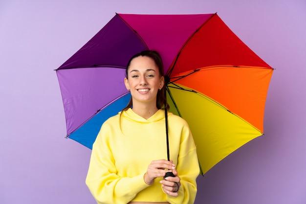 Молодая брюнетка женщина, держащая зонтик над изолированных фиолетовые стены, много улыбается