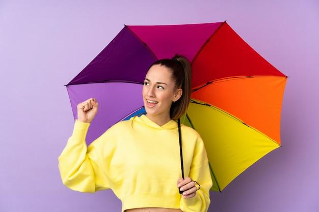 勝利を祝う孤立した紫色の壁に傘を置く若いブルネットの女性
