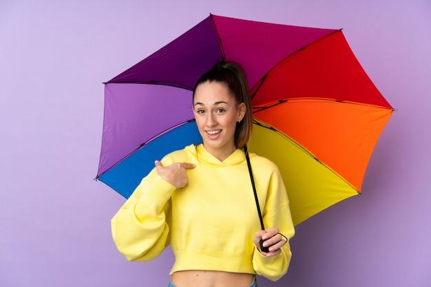 Молодая брюнетка женщина, держащая зонтик над фиолетовым стена с удивленным выражением лица