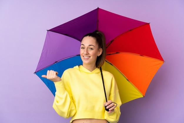 Молодая брюнетка женщина, держащая зонтик над изолированные фиолетовые стены, указывая в сторону, чтобы представить продукт
