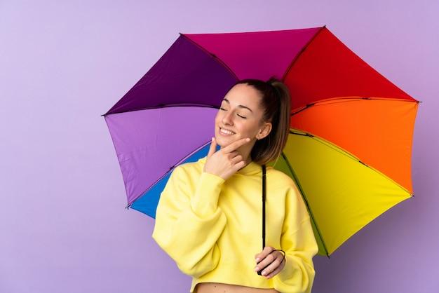Молодая женщина брюнет держа зонтик над изолированной фиолетовой стеной думая идея и смотря сторону
