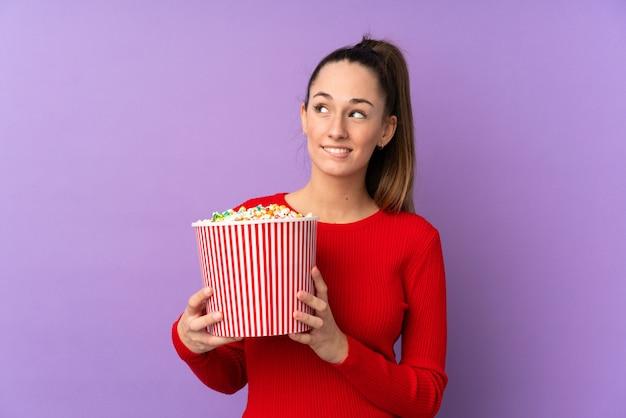 ポップコーンの大きなバケツを保持している孤立した紫色の壁の上の若いブルネットの女性