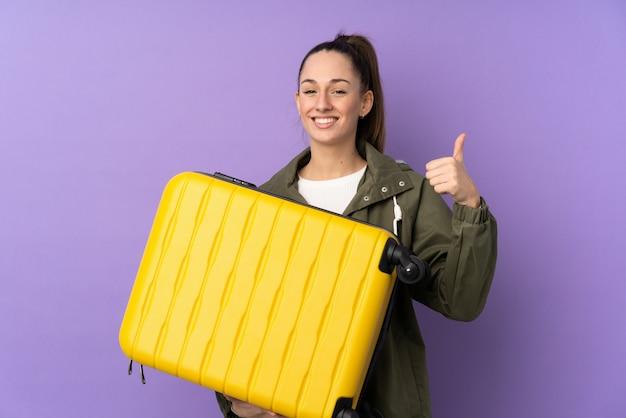 Молодая брюнетка женщина над фиолетовым стена в отпуск с чемоданом путешествия и с пальца вверх