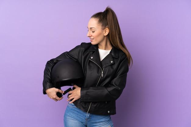 幸せな表情で孤立した紫色の壁の上のオートバイのヘルメットを持つ若いブルネットの女性